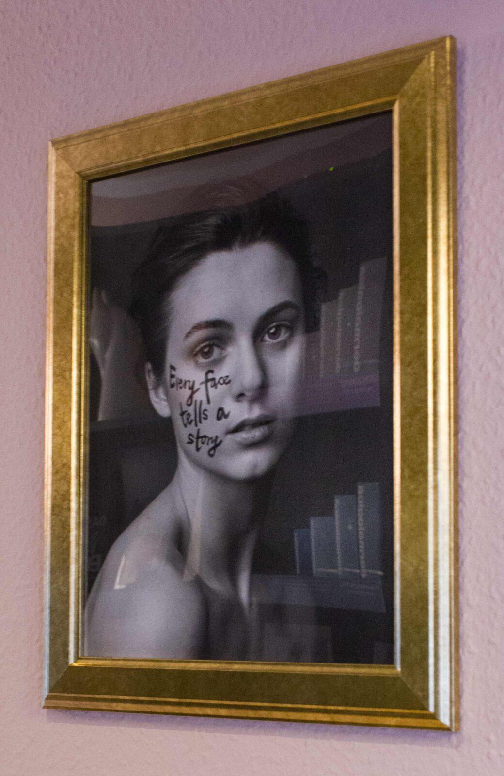 """Bild im Rahmen mit abgebildeter Frau, auf Gesicht geschrieben """"Every face tells a story"""""""